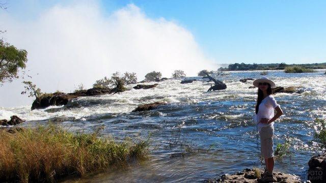 Туристка на берегу реки Замбези на вершине водопада Виктория