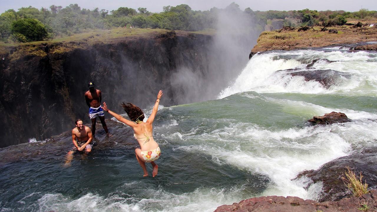Туристы в Бассейне Дьявола на краю водопада Виктория