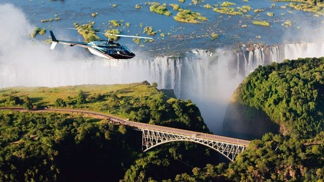 Вертолёт над мостом на панораме водопада Виктория