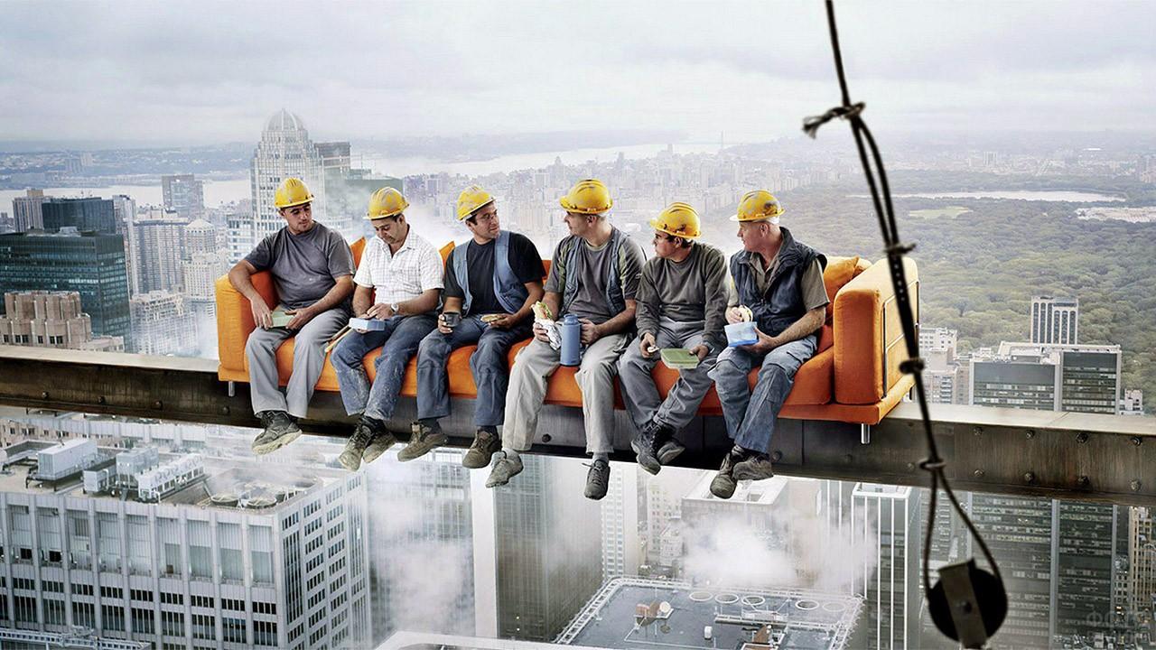 Бригада строителей в касках в фотозоне с диваном на высоте