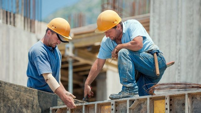 Двое строителей в касках работают на объекте