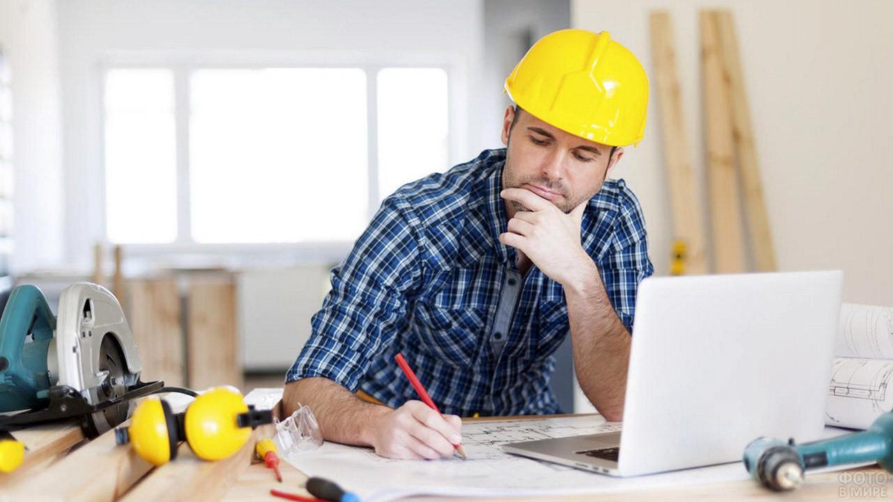 Мужчина в жёлтой строительной каске задумался над проектом