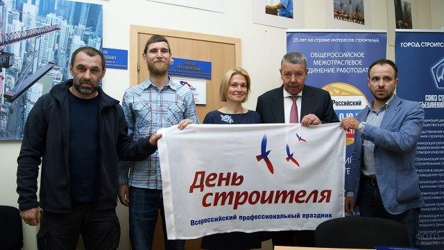 Петербургские строители с флагом в свой профессиональный праздник в офисе