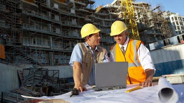 Прораб и инженер на объекте с ноутбуком и чертежами