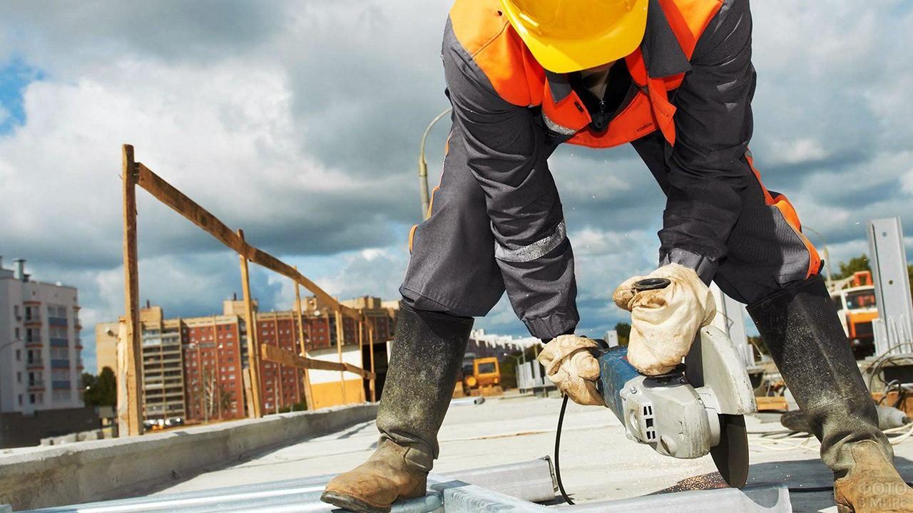 Рабочий с болгаркой на строительном объекте