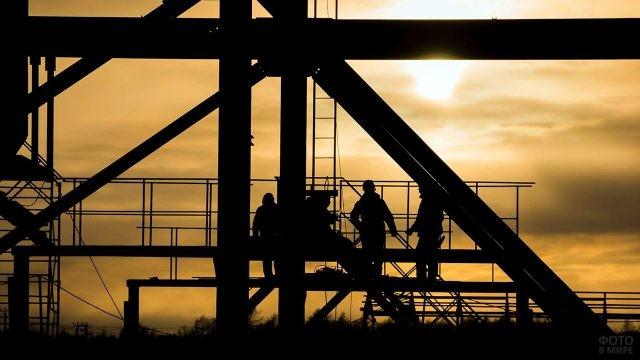 Силуэты строителей на фоне заката