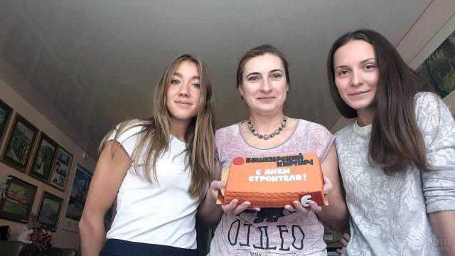 Сотрудницы строительной фирмы с тортом в виде кирпича в свой профессиональный праздник