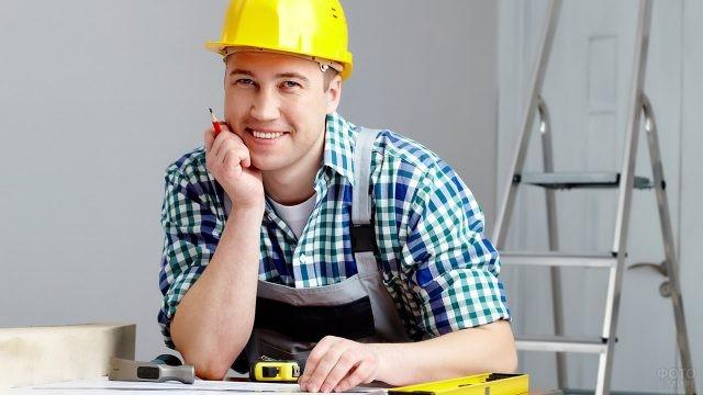 Улыбающийся мужчина в жёлтой строительной каске
