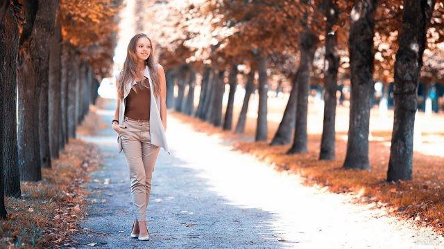 Девушка в брючном костюме гуляет по аллее