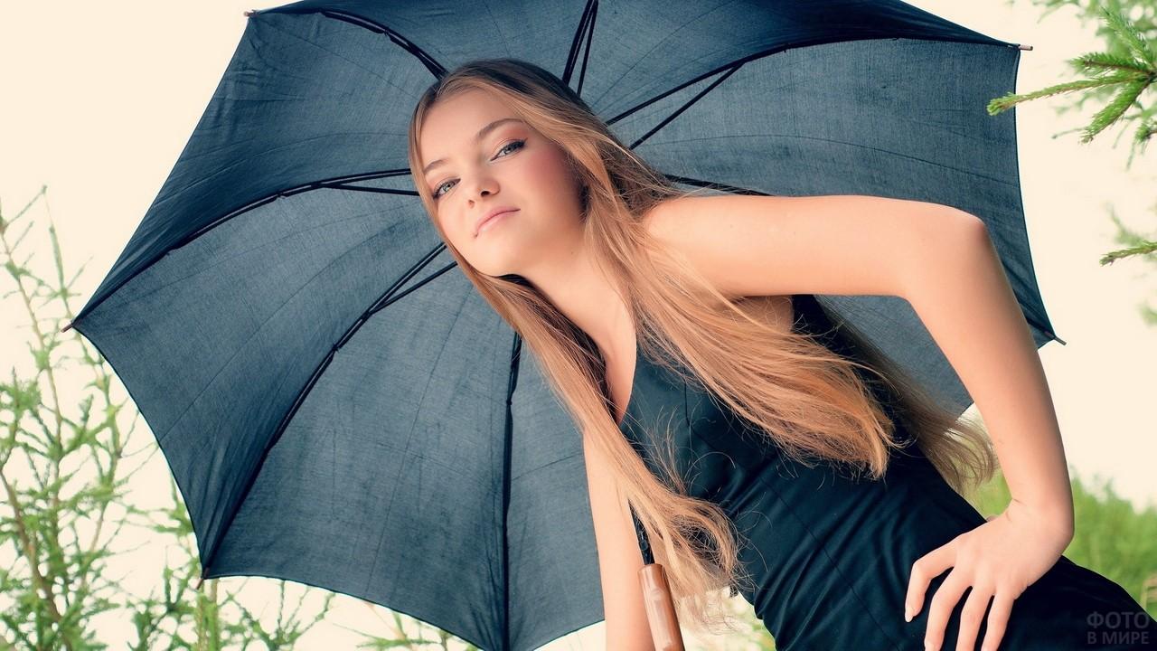 Нежная девушка под синим зонтом смотрит сверху вниз