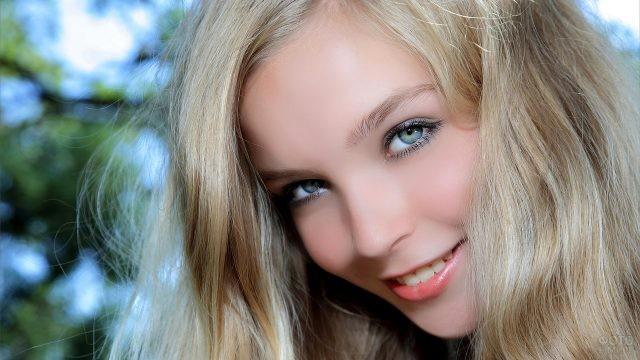 Русая девушка с голубыми глазами на природе