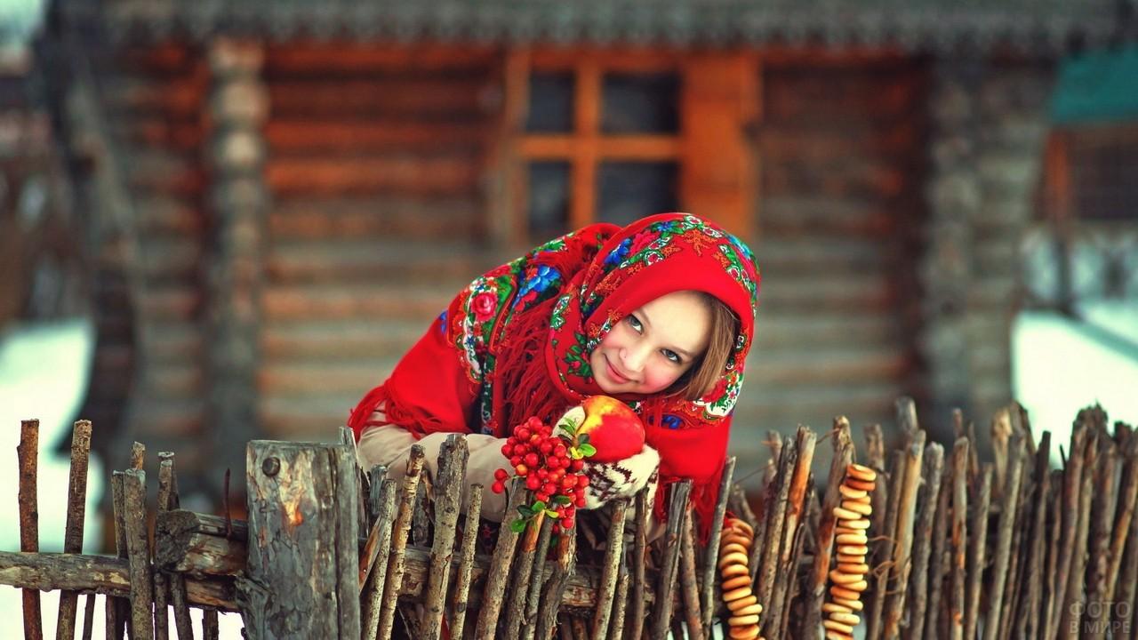 Русская девушка с яблоком возле избы