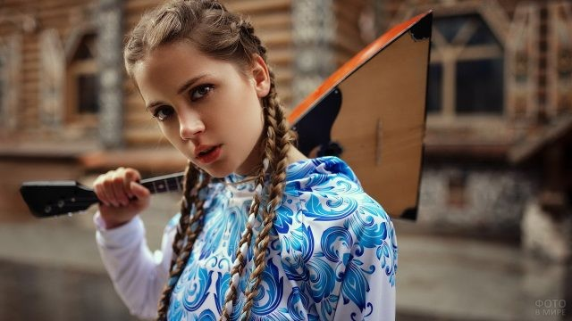 Смелая девушка с косичками и балалайкой на плече