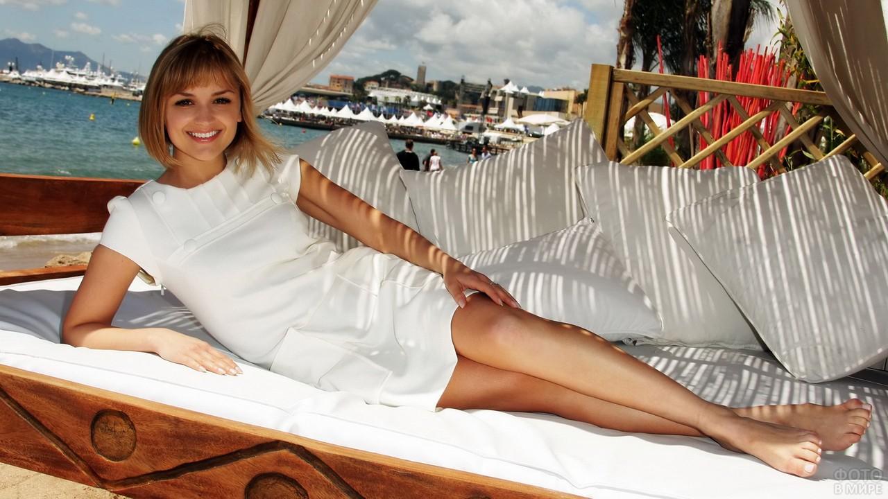 Туристка в белом на пляжном шезлонге