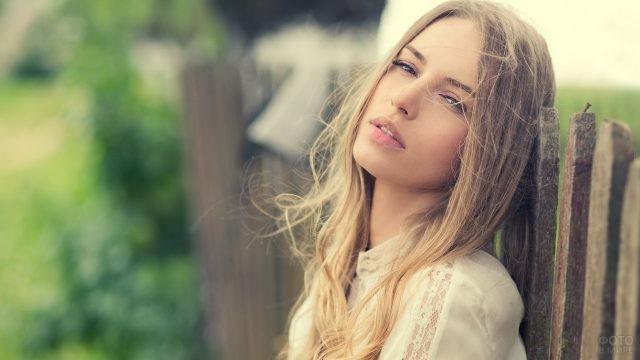 Уставшая девушка облокотилась на деревянный забор