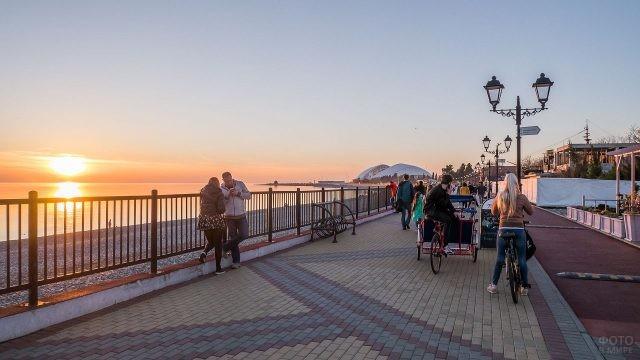 Люди гуляют по набережной на фоне алого заката