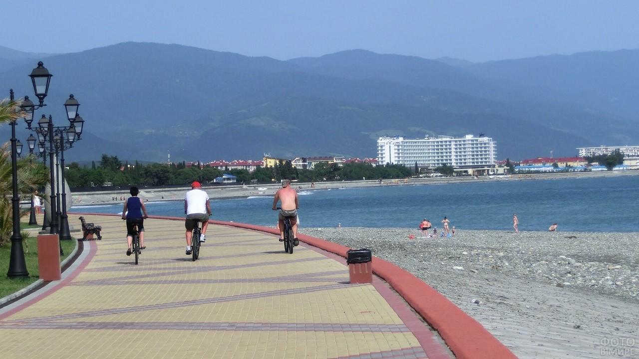 Люди катаются на велосипедах по набережной курорта