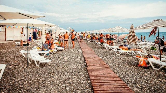 Люди отдыхают на пляже под солнцем