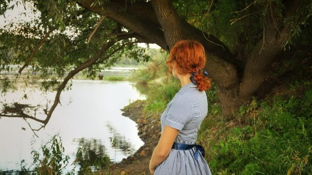 Барышня в клетчатом платье стоит на берегу реки