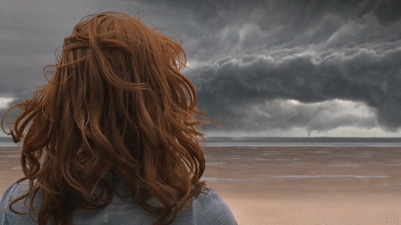 Девушка смотрит на шторм в море