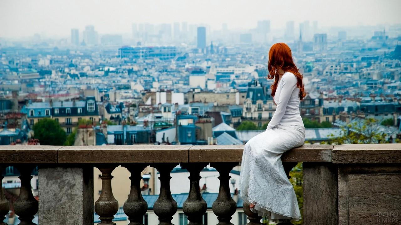 Девушка в белом платье на перилах на фоне города