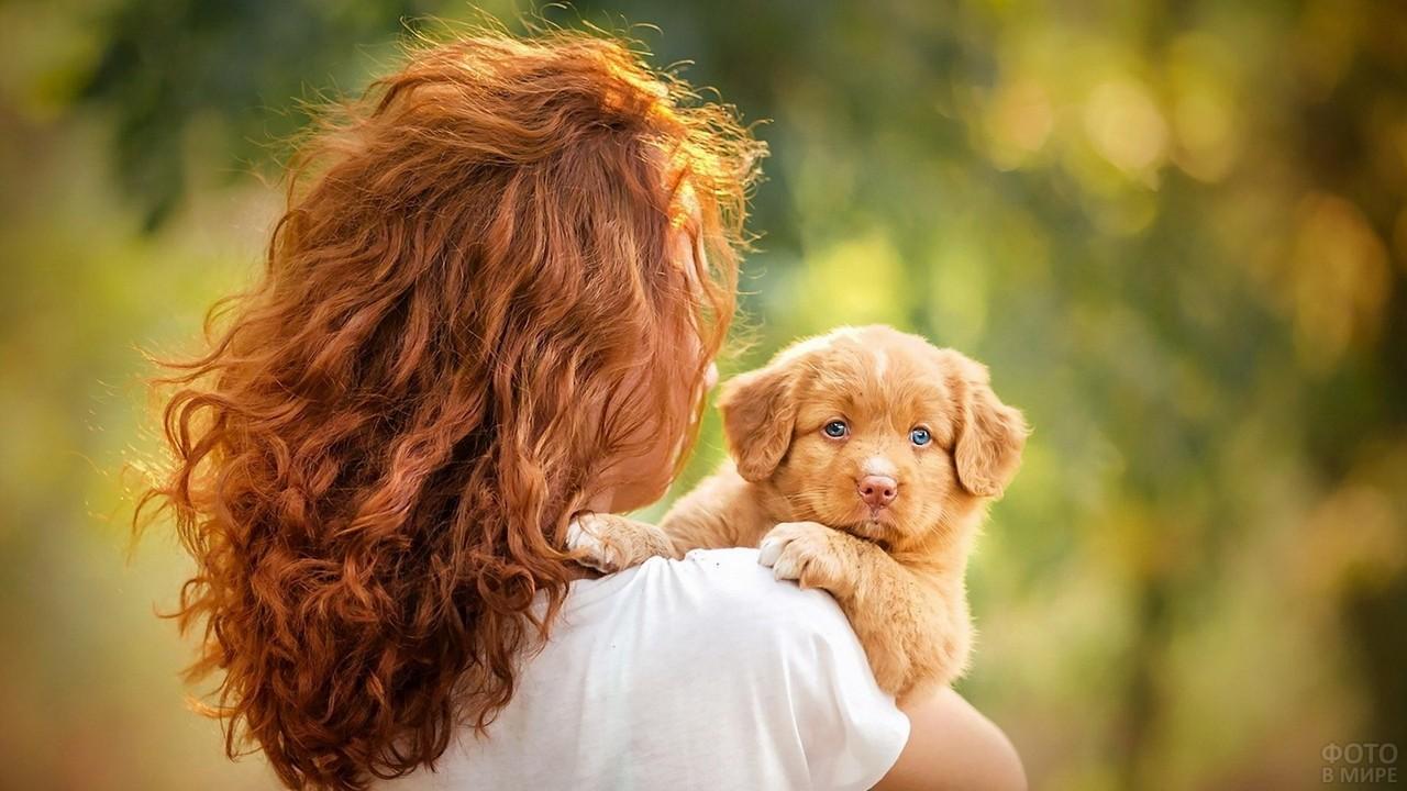 Кудрявая девушка держит на руках щенка