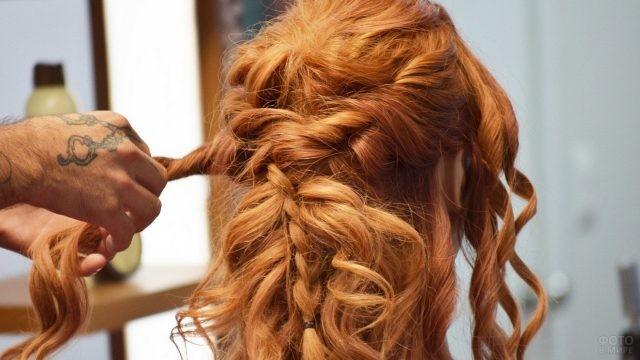Парикмахер делает красивую причёску девушке