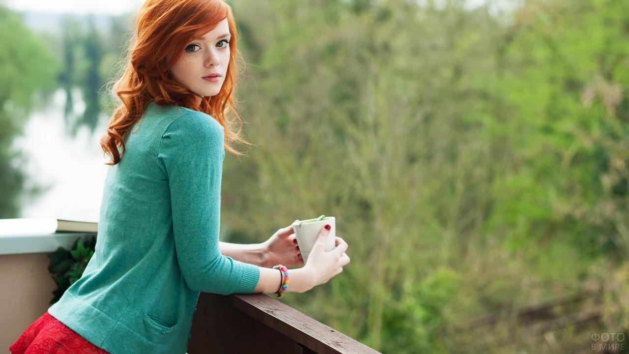 Рыжая девушка на балконе с чашкой