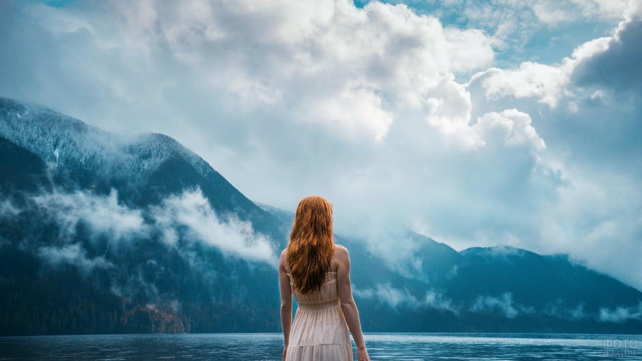 Рыжая девушка на фоне моря и гор