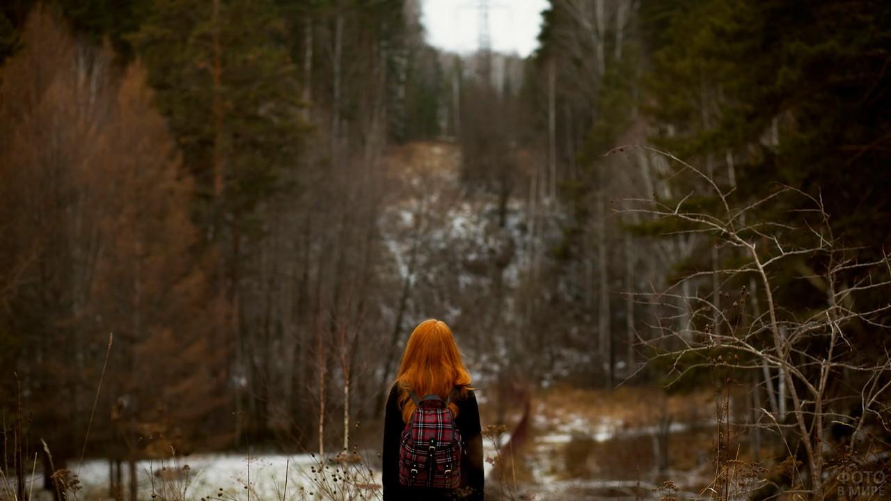 Рыжая девушка с рюкзаком на фоне леса