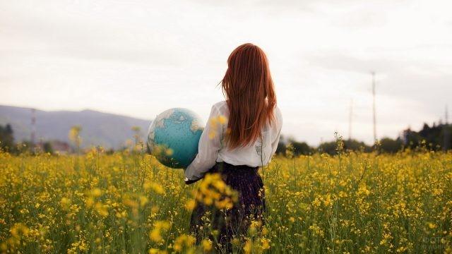 Рыжая с глобусом в руках среди цветов