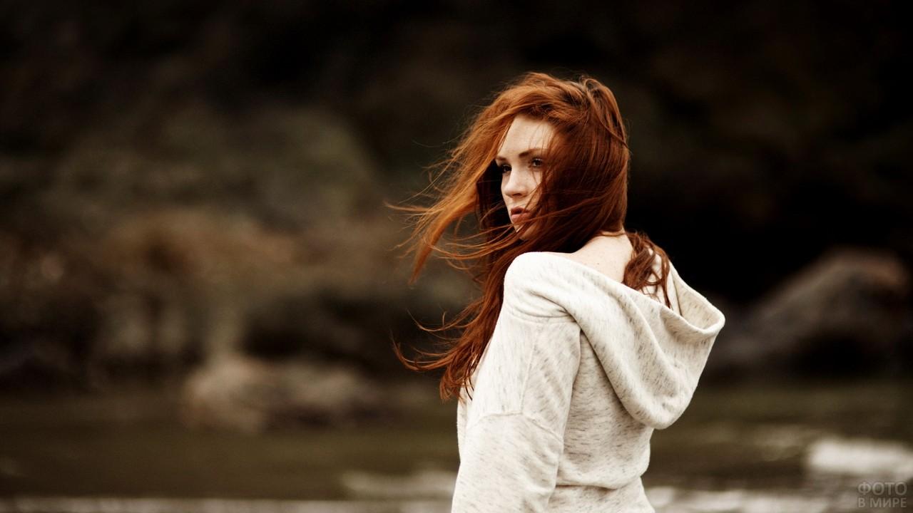 Рыжеволосая девушка обернулась на природе