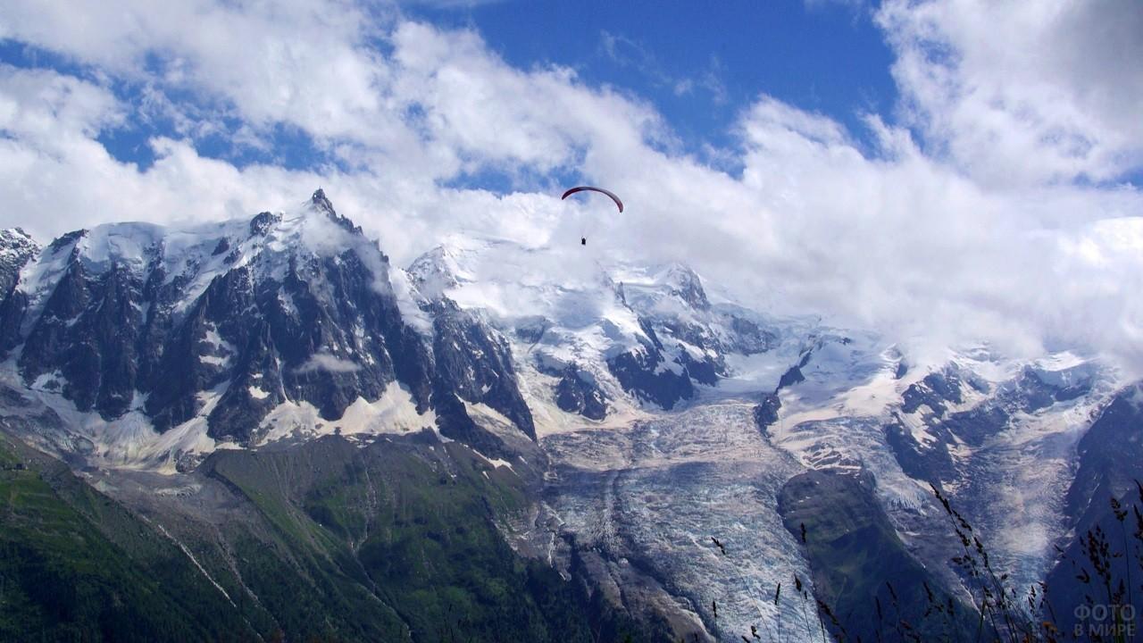 Человек, летящий с парашютом на фоне красивых гор