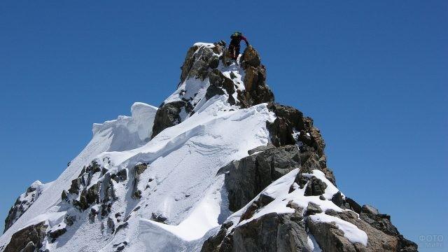 Человек взбирается на вершину горы Монблан
