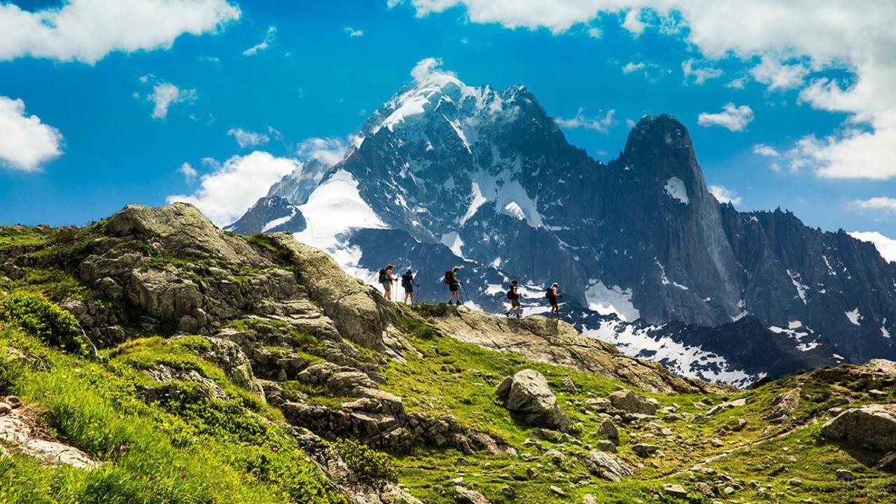 Люди идут по каменистой породе на фоне прекрасных гор