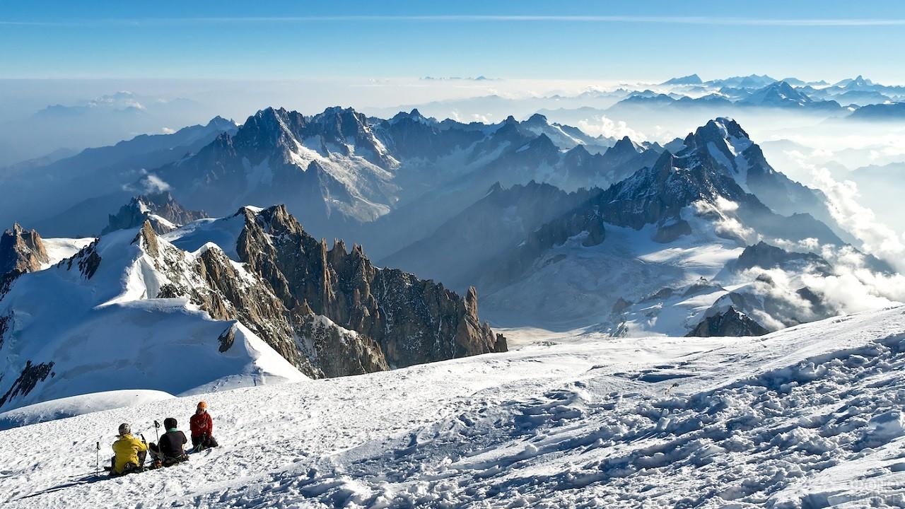 Люди сидят на снегу и любуются прекрасным видом