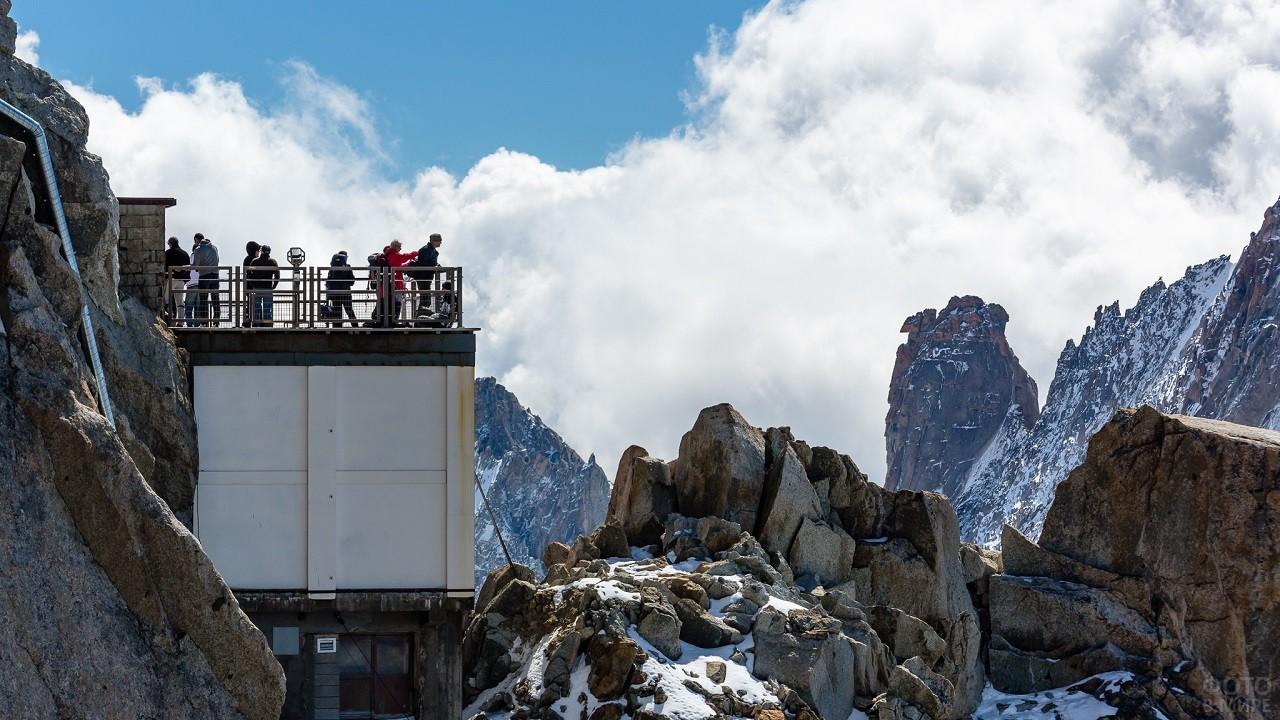 Люди стоят на открытой террасе и любуются видом