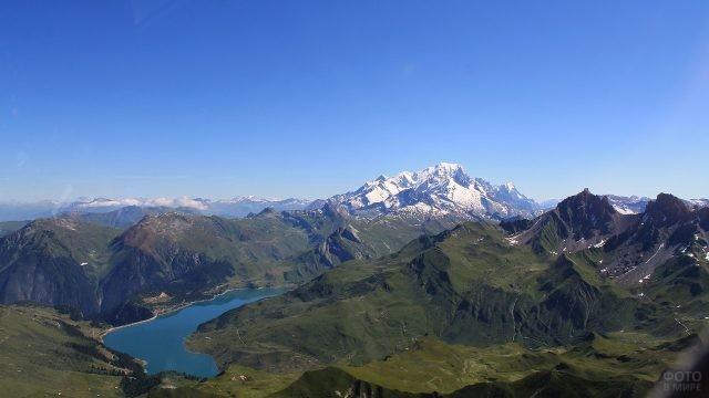 Вид сверху на зелёные холмы и заснеженную гору