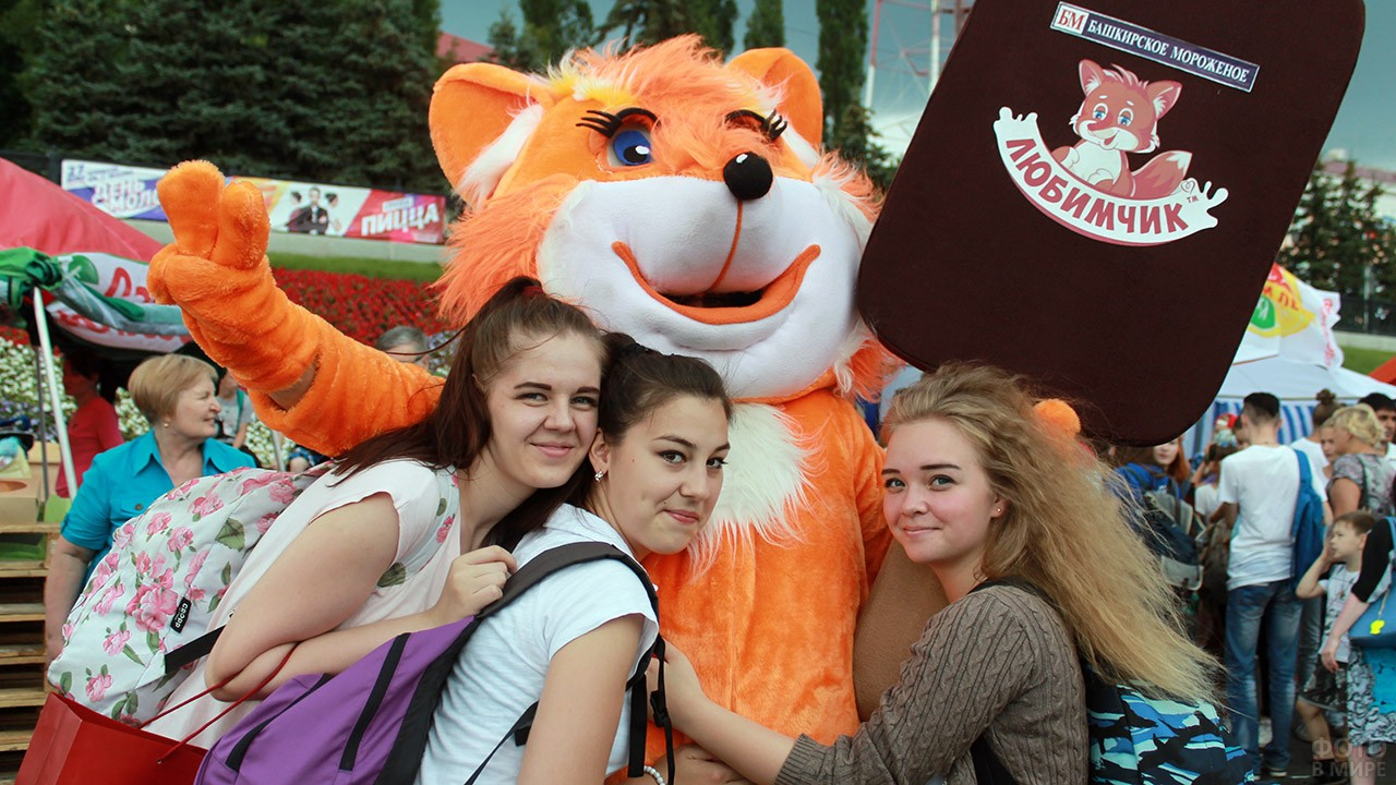 Девушки обнимают аниматора в костюме лисёнка