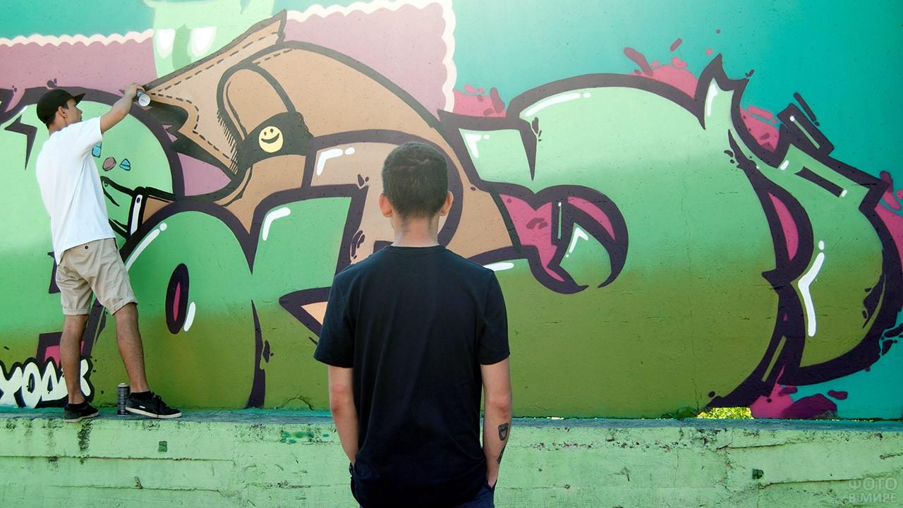 Подросток смотрит как товарищ наносит граффити