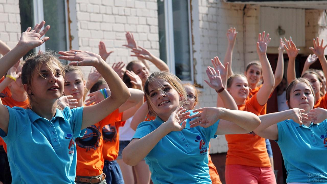 Танцующие школьницы в яркой форме летнего лагеря