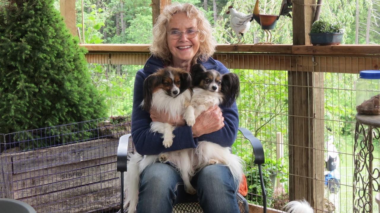 Женщина держит двух собак на руках сидя в кресле