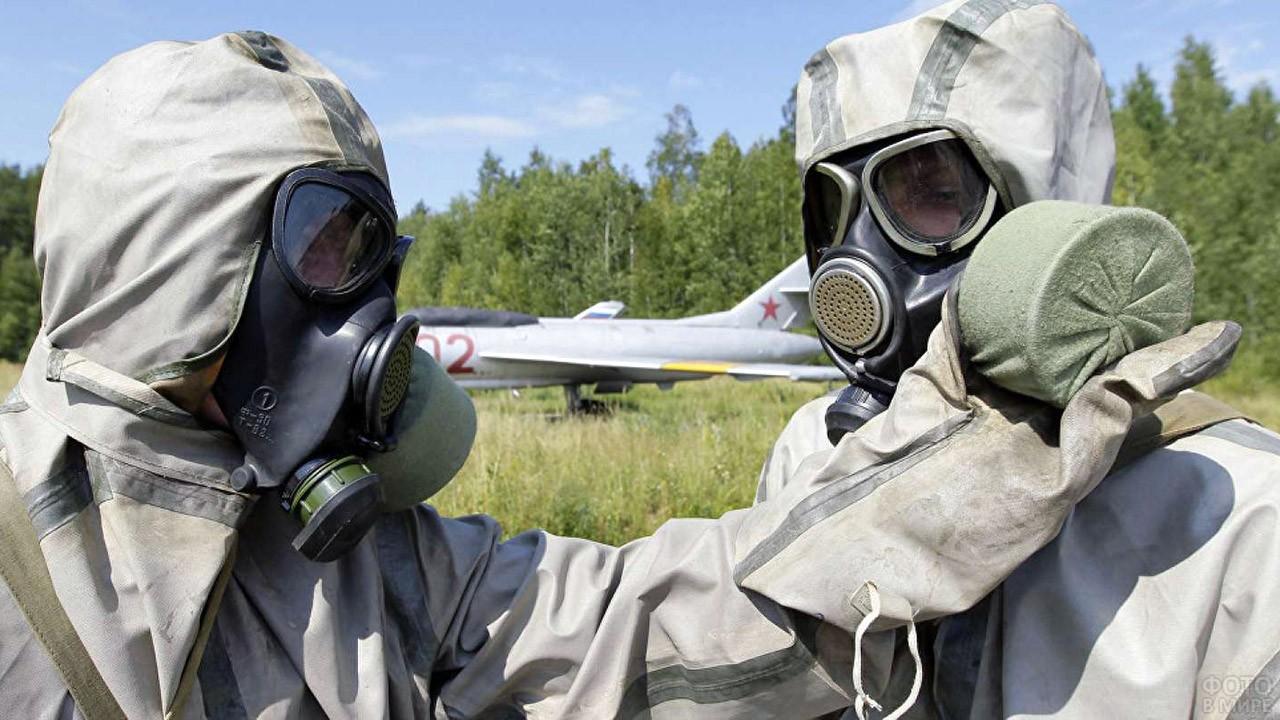 Два человека в костюмах химзащиты на лётном поле