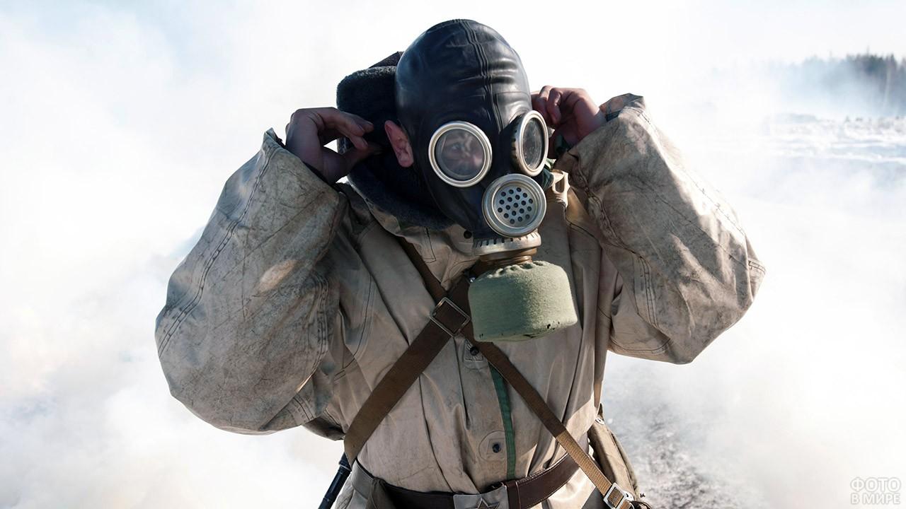 Солдат РХБ защиты надевает противогаз посреди задымлённого поля