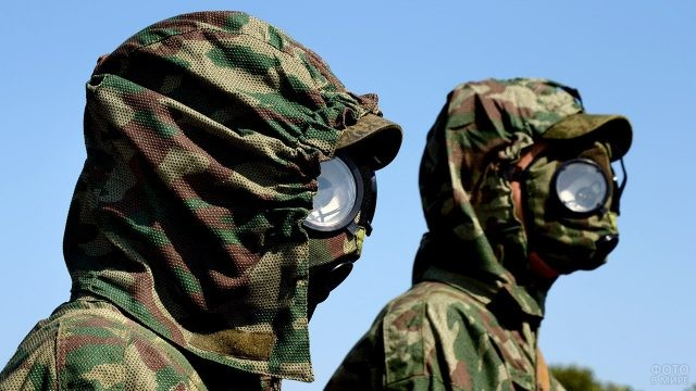 Солдаты химзащиты в камуфляжных костюмах с противогазами