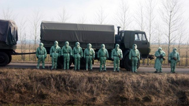 Солдаты РХБ защиты рядом с колонной тяжёлой техники
