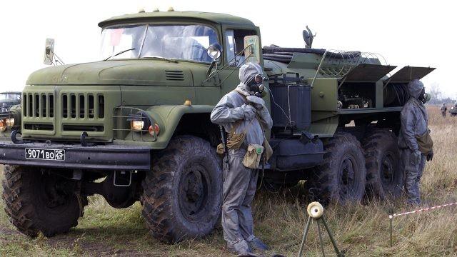 Солдаты в костюмах химзащиты охраняют АРС РХБЗ