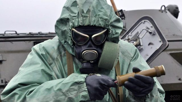 Военный в костюме химзащиты смотрит на дозиметр радиации