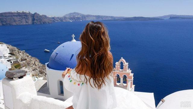 Длинноволосая девушка в белом на Санторини смотрит на море