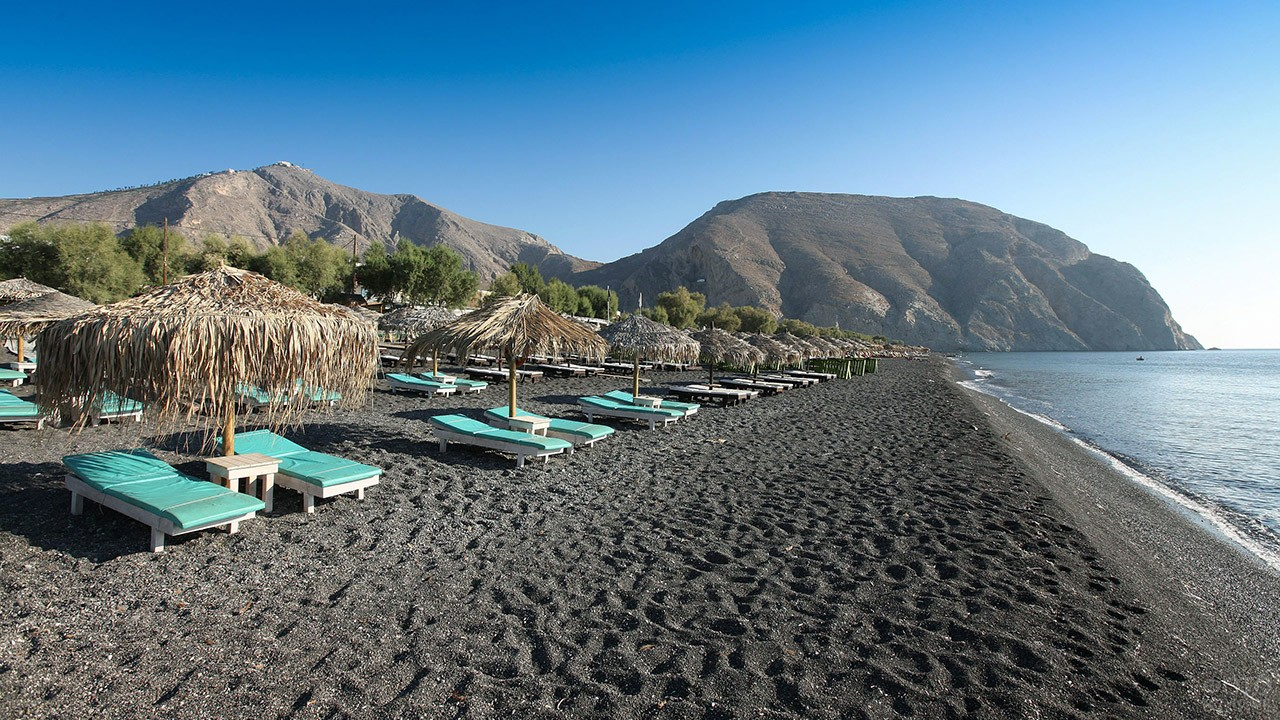 Шезлонги на вулканическом песке пляжей Санторини
